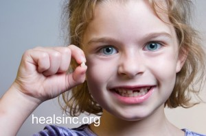 girl holding missing tooth healsinc
